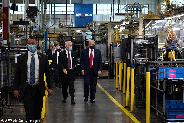 President Trump wears a face mask as he walks through the Whirlpool factory