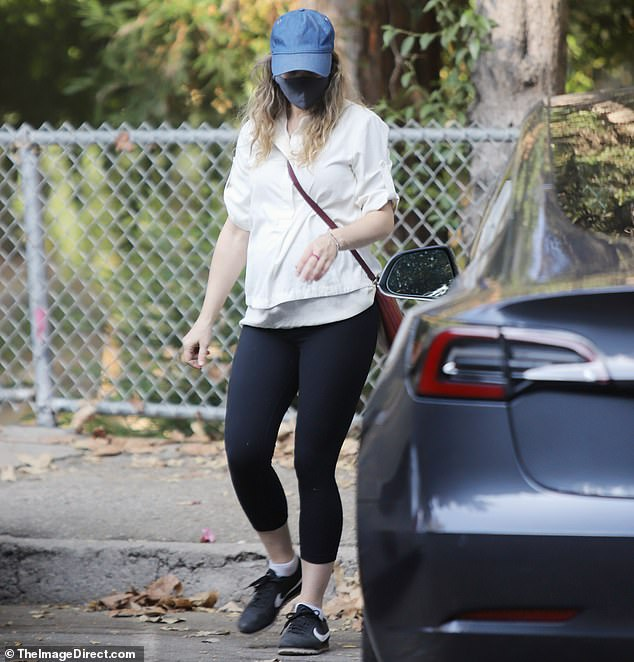 Street style:She stuck to a simple outfit of a sweatshirt and leggings, accessorizing with a blue baseball cap and a cross-body bag