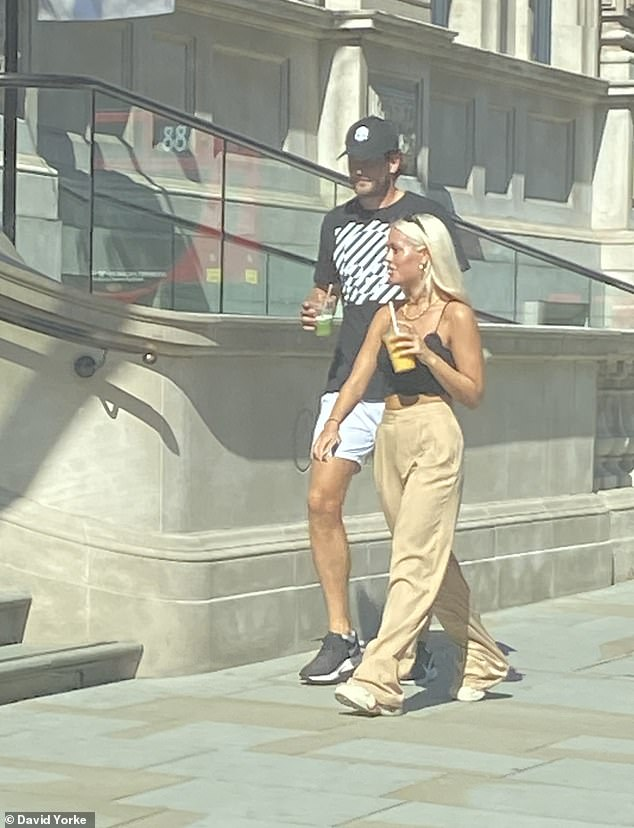 Close: Lewis Burton and rumoured girlfriend Lottie Tomlinson add further fuel to romance rumours as they head out for a sunny stroll on Friday