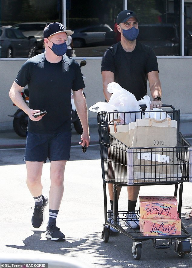 Loaded up: The 44-year-old Modern Family star and his hubby of seven-years wore matching cloth face masks as they ventured through the parking lot with their full cart