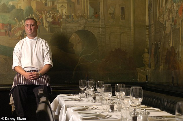 """Pictured:Chef Richard Oxley sitting in the restaurant with the mural """"Expedition in persuit of rare meat"""" painted by Rex Whistler between 1926 and 1927 in the background"""