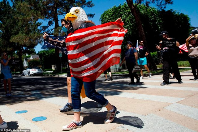 Pictured: A demonstrator wears an eagle mask and holds a US flag during as they march in support of the US president during a WalkAway rally on Saturday in Beverly Hills