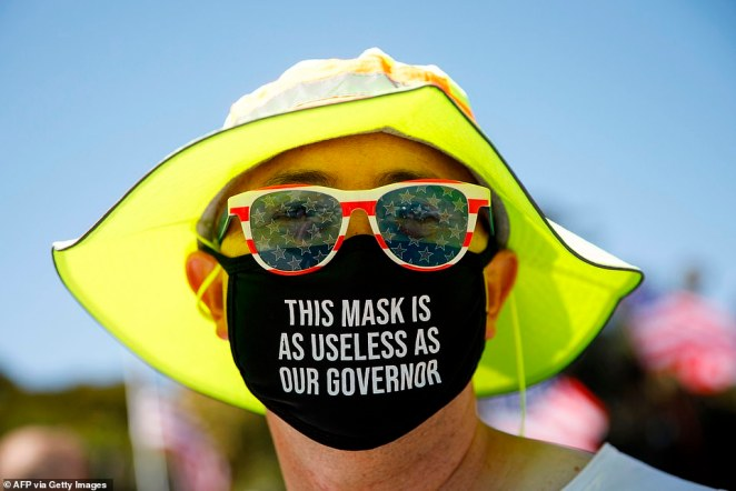 Pictured:A demonstrator wears a face mask reading 'This mask is as useless as our governor' referring to the governor of California during a WalkAway rally on Saturday