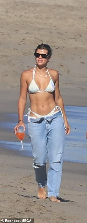 At a different point: The daughter of Lionel Richie also covered up – to a point – in unbuttoned jeans that still showed a hint of her white thong swimsuit bottoms