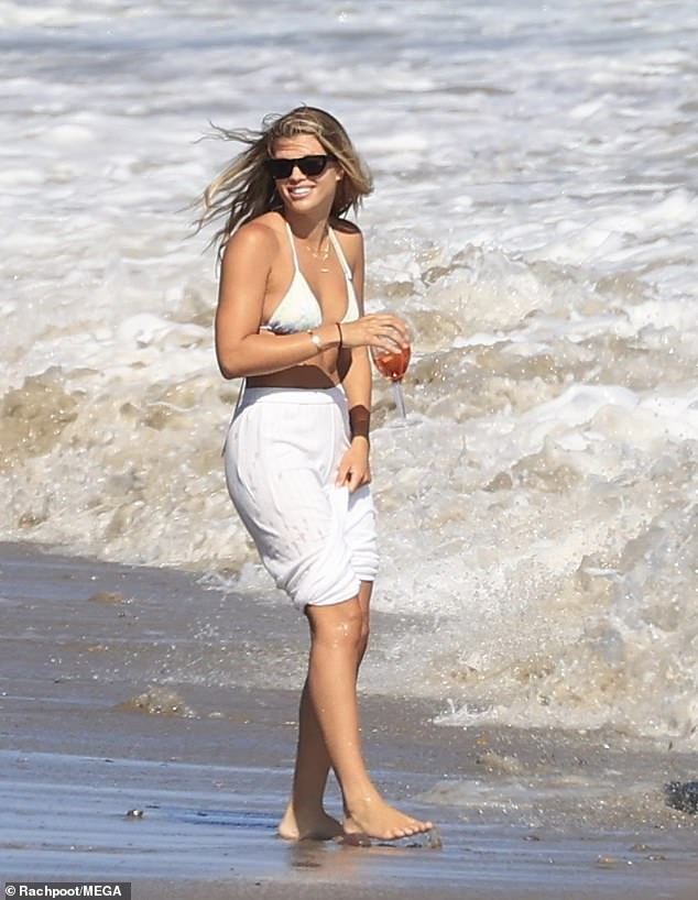 During her fun-filled beach day: Sofia's hair was down as she waded in the surf, wearing a white beach pants