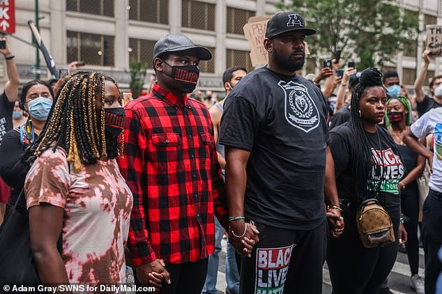 Ingram (second left) stood outside the precinct for a few moments with protesters before heading in to speak with officials.  An NYPD spokeswoman said Ingram, 28, was booked on a charge of second-degree assault in connection with a June 14 incident during a protest in Midtown Manhattan