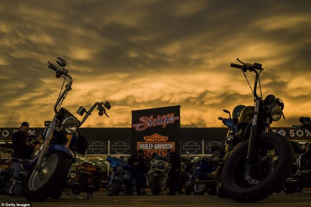 The sunset on Saturday evening lights up storm clouds over the Sturgis Harley-Davidson dealership