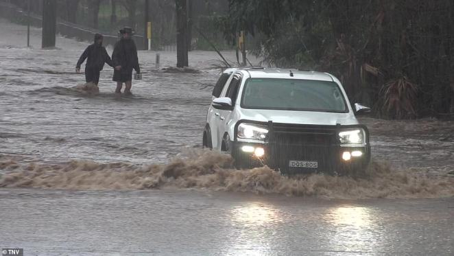 One couple were seen holding hands as they trudged through the water just to cross the road as the town was battered by intense rainfall in Berry on Saturday