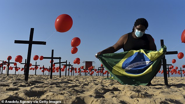 Brazil has become the second country to surpass 100,000 deaths from coronavirus after confirming more than three-million cases and100,477 deaths. Pictured, a tribute for the victims is held on Copacabana beach in Rio de Janeiro