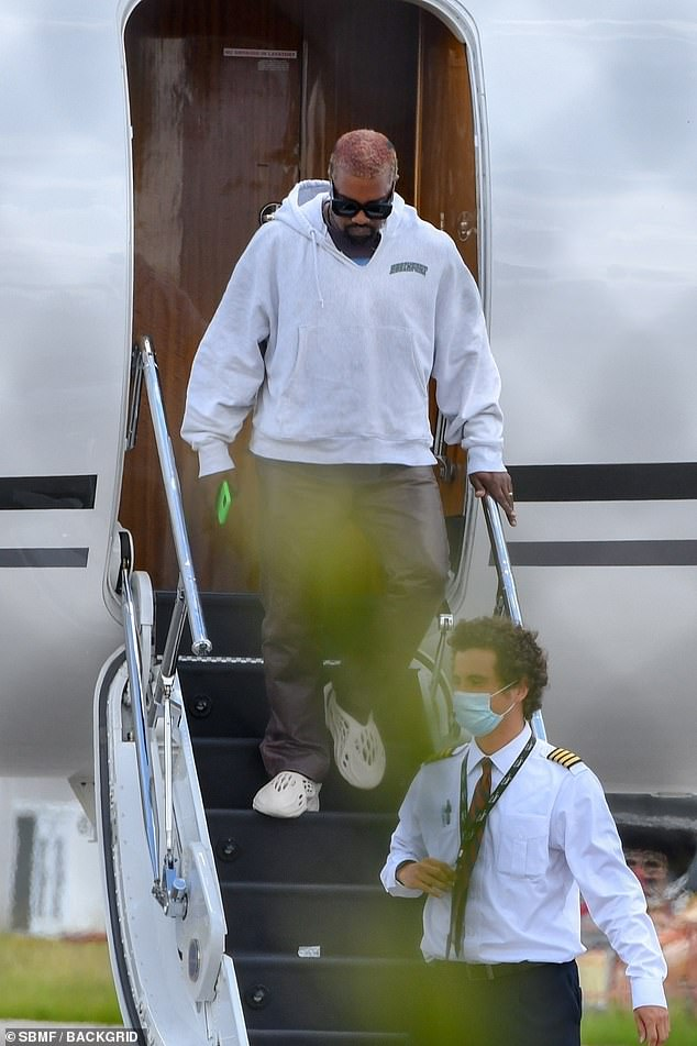 Looking healthy: West appeared at ease, holding his phone, and gliding down the plane's stairs with ease