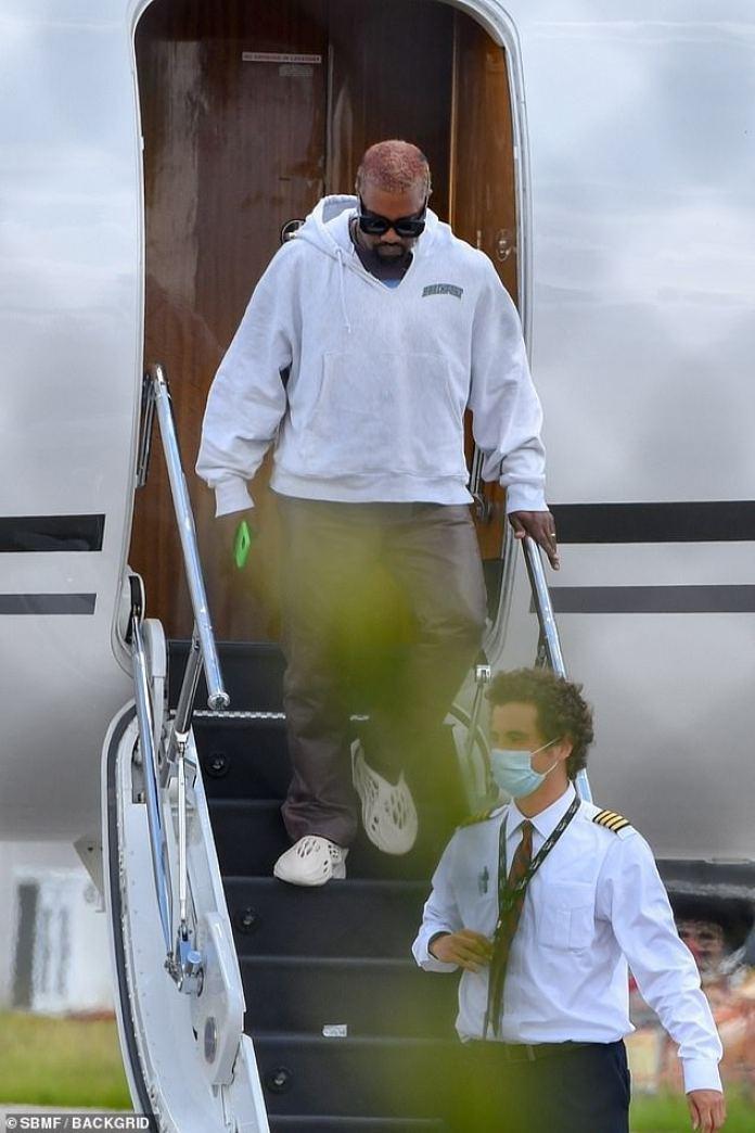 Luciendo saludable: West parecía cómodo, sosteniendo su teléfono y deslizándose por las escaleras del avión con facilidad