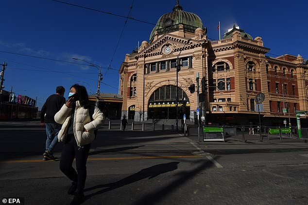 Two pedestrians walk outside a deserted Flinders Street Station in Melbourne on Monday amid stage four restrictive measures in the city