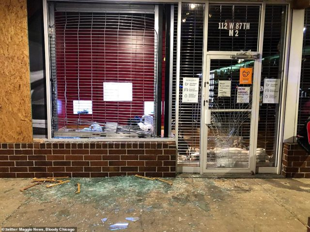 Stores along Magnificent Mile in Chicago were hit by a wave of looting last night with shop fronts devastated, like this City Sports store which looters tried to storm the front of, after a day of tense stand-offs between police and protesters