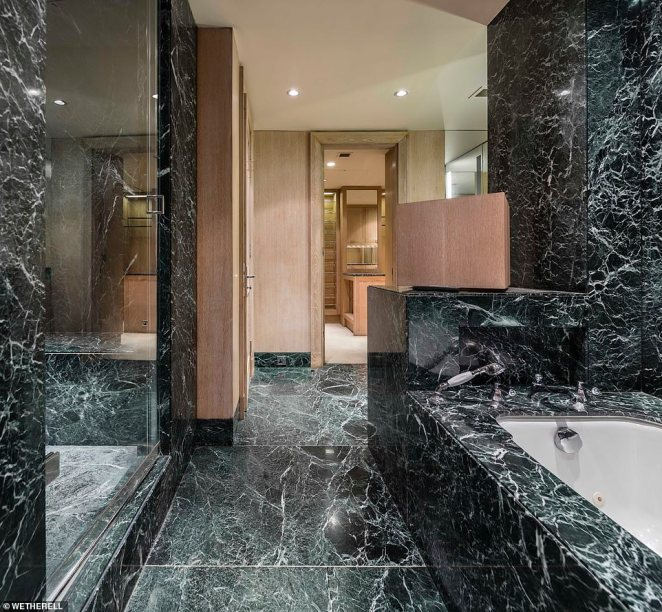 Both 'his and hers' dressing rooms open out into spacious 'his and hers' master bathroom, which features dramatic dark marble tiling