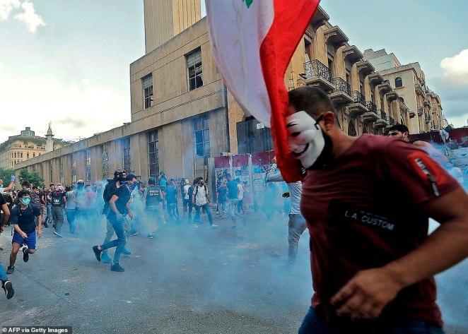 Lebanese protesters run from tear gas fired by security forces today in Beirut today.Many see the blast as a symbol of corruption and incompetence among the country's elite, and protests have broken out after months of political and economic meltdown.