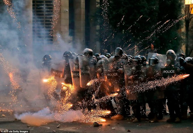 Firecrackers thrown by protesters explode in front of riot police amid clashes in the vicinity of the parliament in central Beirut on August 10, 2020