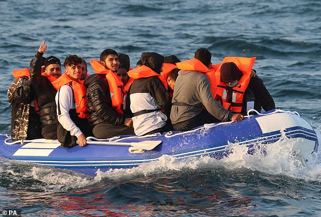 We're over here! The young passengers aboard the crowded dinghy smile with relief after being spotted