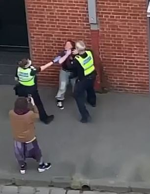 A man with a purple scarf then appears. He can be seen filming the incident from the footpath as another police officer shows up