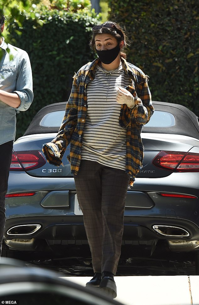 Casual chic:Charli looked relaxed as she teamed a yellow-and-blue plaid shirt with a grey striped jumper for the occasion