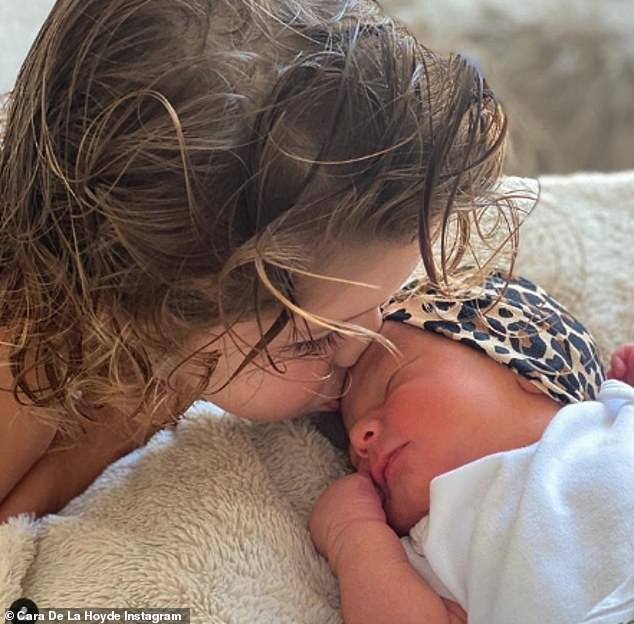 Baby: Cara De La Hoyde has revealed her husband Nathan Massey nearly missed the birth of their daughter because he was asleep at home (pictured son Teddie, two, kissing Delilah)