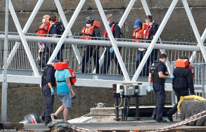 Migrants disembark after arriving at Dover harbour this morning, the latest to arrive after days of constant crossings from Calais to the UK