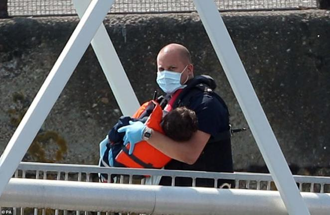A Border Force official brings a child to land after vessels crossed from Calais to the UK yesterday