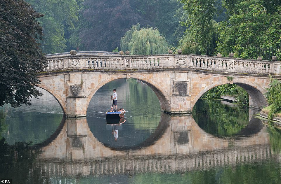 People enjoy the hot weather as they take a punt trip along the River Cam in Cambridge this afternoon