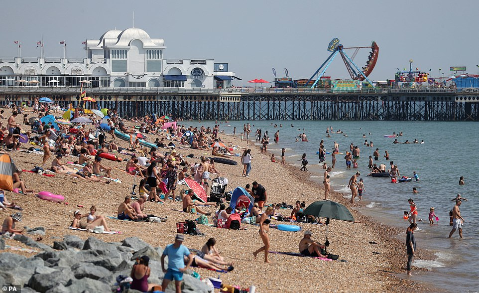 People enjoy the hot weather on Southsea beach in Hampshire this afternoon as the heatwave continues
