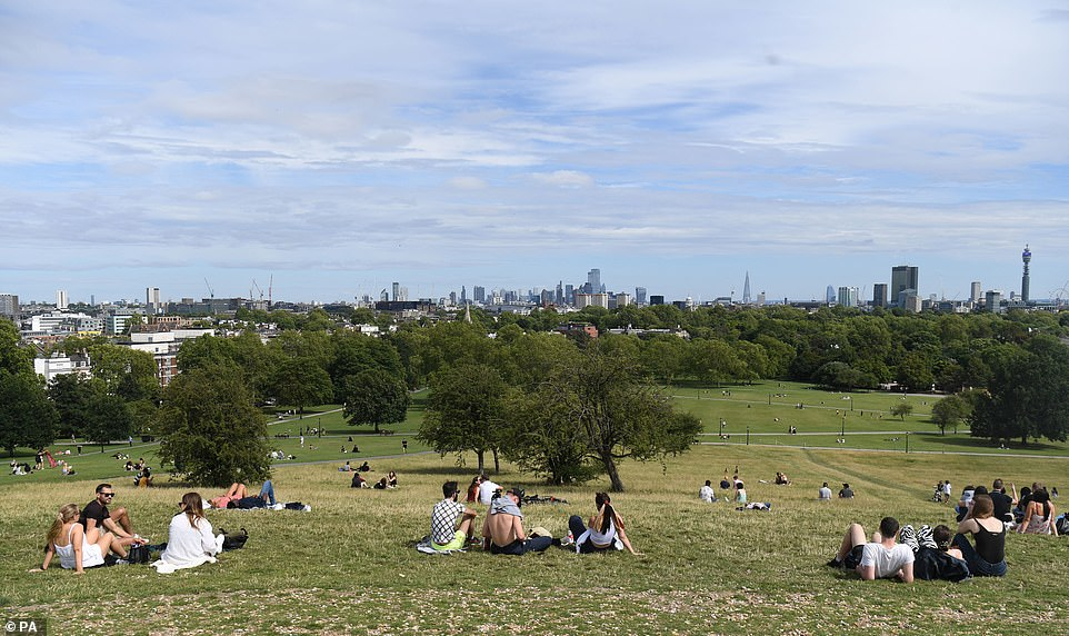 People enjoy the warm weather on Parliament Hill in North London this afternoon