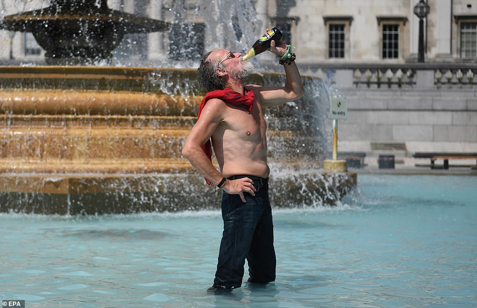 A topless man drinks cider in the sunshine at the fountains at Trafalgar Square in London this afternoon