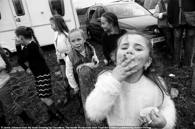 A group of traveller girls stand in front of a caravan with one of them looking at the camera while posing with a cigarette at the camera in this picture by US photographer Jamie Johnson