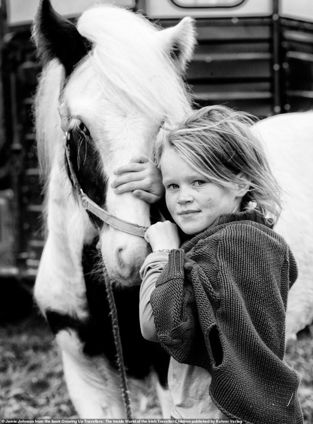 A young traveller girl pets a horse in this photograph taken by US photographer Jamie Johnson. Horse ownership is considered one of the last links to the community's nomadic way of life