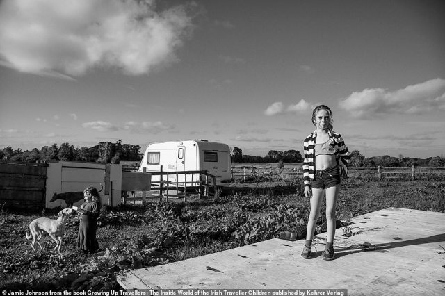 A young girl poses for a photograph as another feeds a greyhound in this image taken by US-based photographer Jamie Johnson, who gained the trust of an Irish traveller community