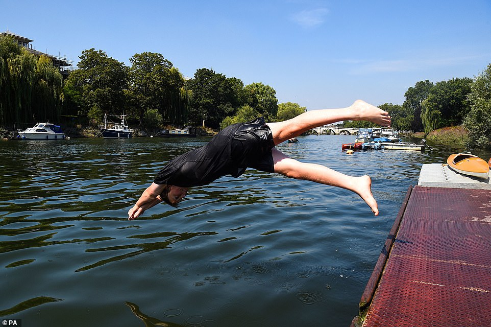 Danny Merva, 14, jumps into the River Thames from a pontoon at the Richmond Canoe Club in South West London today