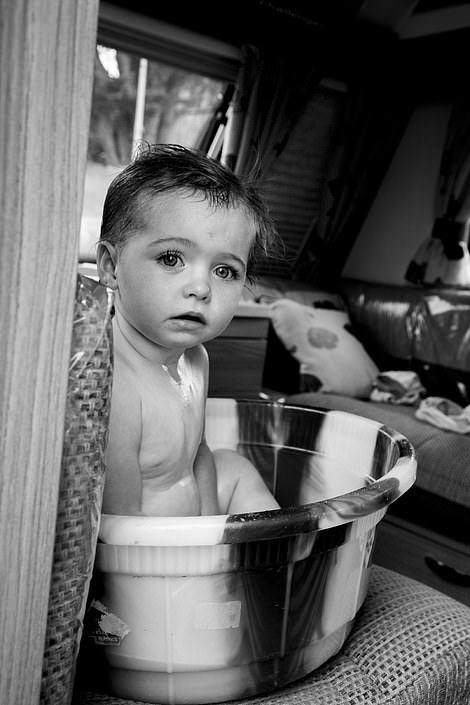 A baby takes a bath in a washing up bowl