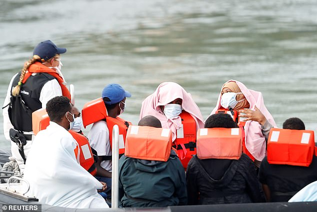 Migrants react are brought to Dover harbour by Border Patrol in Dover, August 11