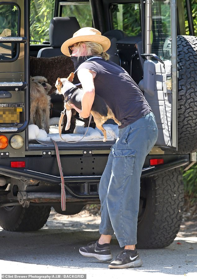 Attentive: Portia huddled her dogs into the back of her vehicle