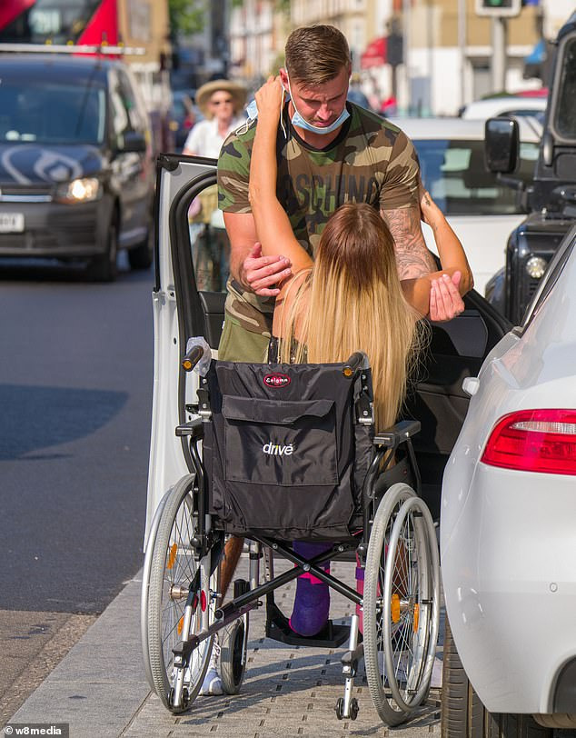 Knight in shining armour:The former glamour model, 42, appeared downcast as she heavily relied on her boyfriend Carl Woods, 31, to help her out of the car and into a wheelchair