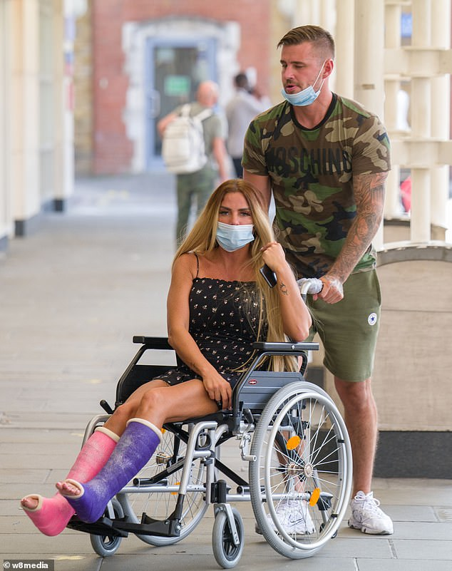 Having a bit of fun:Katie ensured she made her arrival known as she showed off her customised her leg casts which were covered in pink and purple glitter