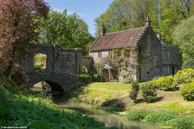 Within the grounds are several other buildings, including the very pretty three-bedroom Gardeners Cottage (pictured) which is accessed over a bridge and has a high castellated stone wall, complete with cruciform arrow slits which forms a screen to the walled garden beyond