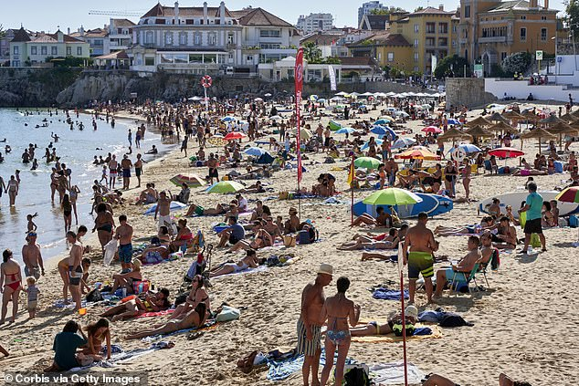 Despite Portugal having a lower rate of new Covid-19 cases in the past seven days than a number of countries on the government's exemption list, travellers entering the UK from Portugal are required to self-isolate on their arrival in the UK. Pictured: Beachgoers crowd Praia da Duquesa, in Cascais, Portugal. on August 09, 2020 as tourism slowly returns