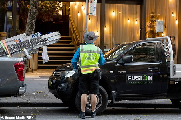 Parking fines issued by City of Sydney Council totalled over $14 million in the last financial year and $24,239 per day in May and June (parking ranger on Pitt St in Sydney pictured)