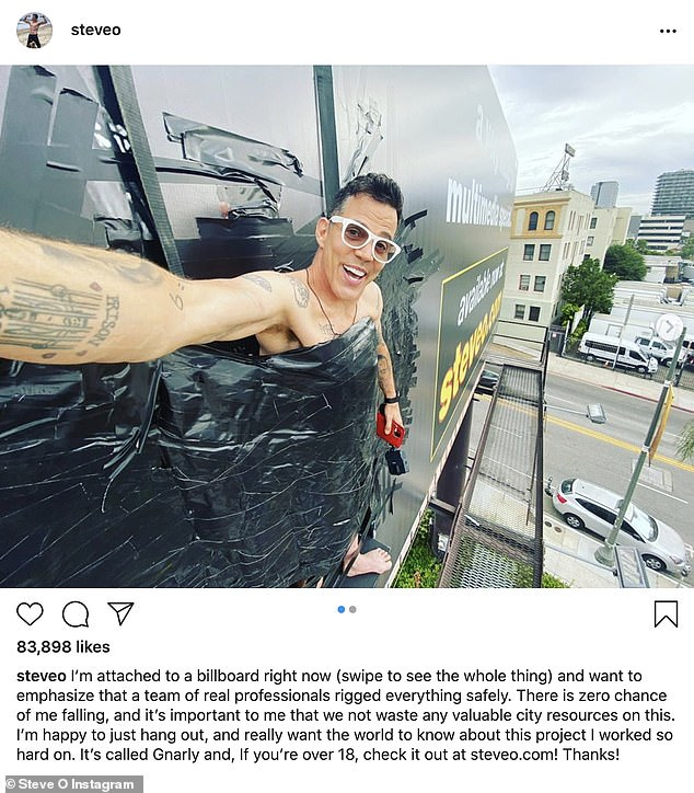 High above: Steve-O earned the attention of passerbys and police after duct taping himself to an LA billboard on Wednesday. Cops stopped by the scene after he was reported on the Citizen app