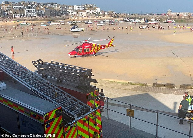 Locals stand on the beach as the air ambulance arrives following the fire at the beachfront bar