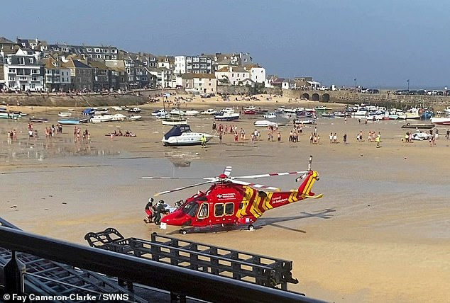 An air ambulance arrives to take the casualty away following the blaze at the tourist hotspot