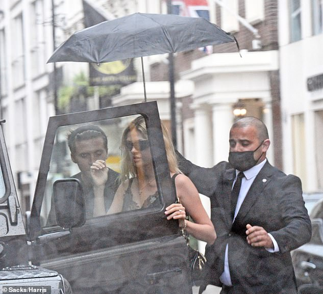 Care: Nicola was looked after during the trip by Brooklyn and a member of staff who sheltered her from the rain with a black umbrella