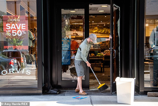 Workers clean up broken glass at an Orvis store after violence broke out on Monday night