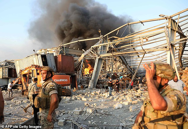 Lebanese firefighters work at the scene of an explosion in the Lebanese capital on August 4