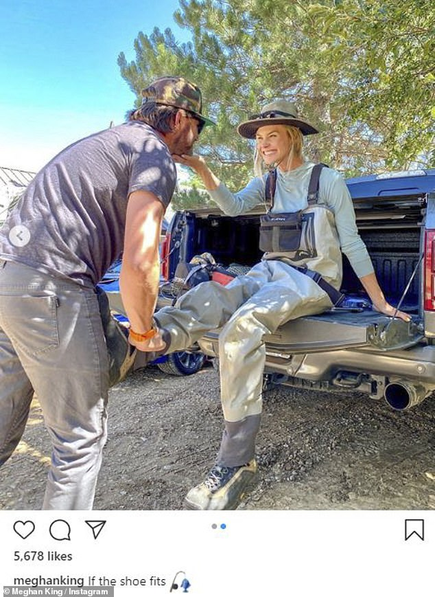 A regular Cinderella:The mother-of-three, 35, sits in the back of a pickup truck, wearing a long-sleeve light blue shirt and a pair of heavy duty-looking tan fly fishing overalls