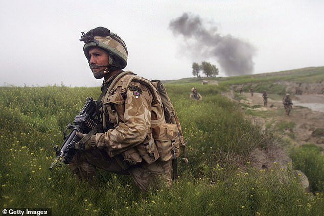 A Royal Marine watches for Taliban movements after an airstrike was called in on a Taliban position on March 18, 2007 near Kajaki in the Afghan province of Helmand